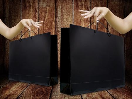 Glossy boodschappentas in dame hand met houten achtergrond