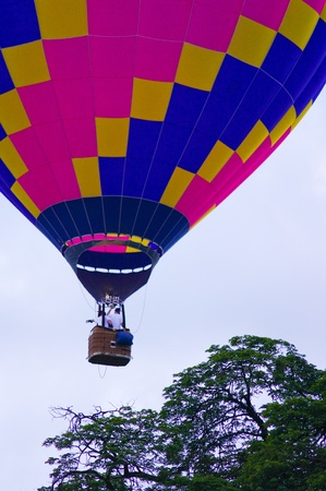 Hot air balloon with flyer in the sky with tree background photo