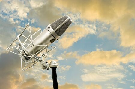 Classic Microphone and cloudy sky at sunset time photo