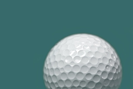 Golf ball on green background photo