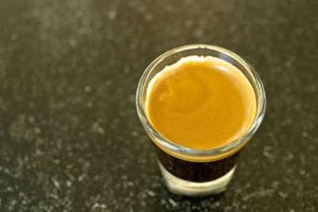 Een schot van espresso op de klassieke borrelglas Stockfoto