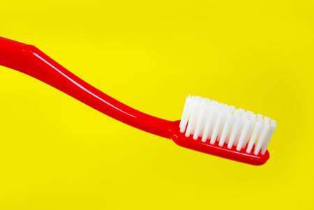 Red toothbrush on yellow background Stock Photo - 12803662