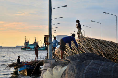 Choburi, Thailand - March 10, 2012 : Undentified fishermans carry bamboo stick to fisherman boat at jetty of Siracha, Chonburi, Thailand.