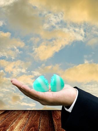 Broken easter egg on businessman hand photo