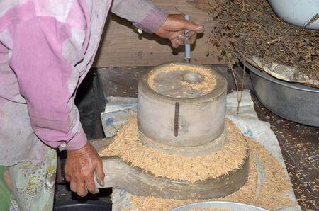 millstone: Farmer milling paddy rice with millstone
