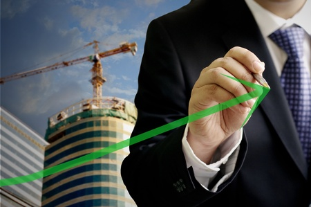 Businessman write a grow up green arrow with construction site background photo