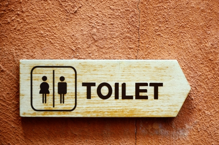 Wooden toilet sign on color wall photo