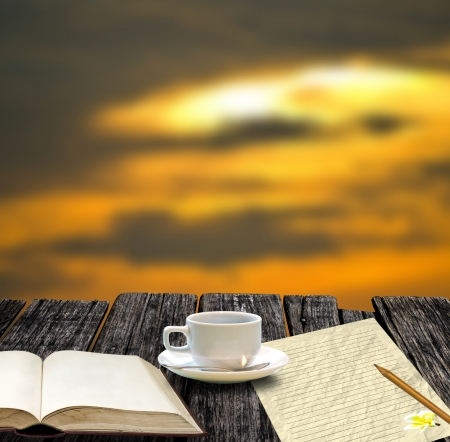Coffee cup with blank book and note paper in morning time photo