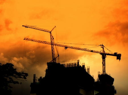 Crane on tower in construction site silhouette with sunset sky photo