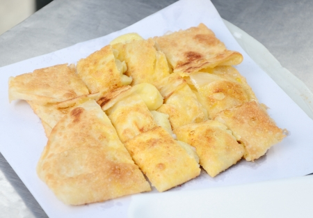 Dessert style of fried Roti with banana cooking on the street in Bangkok, Thailand photo