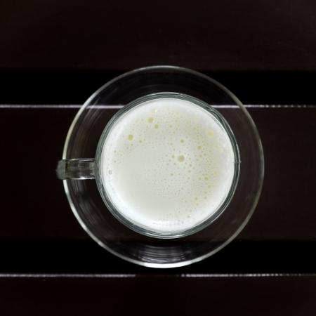 vaso de leche: Taza de leche caliente a la mesa Foto de archivo