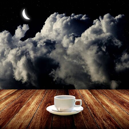 Hot coffee on wooden table with night sky  photo