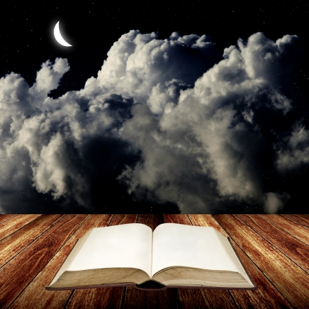 Open blak book on wooden table with night sky photo