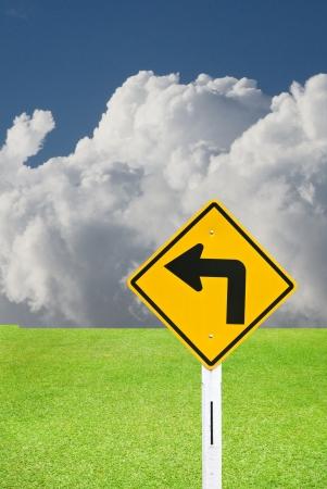 turn left: Girare a sinistra segno con una bella prato verde e il cielo nuvoloso