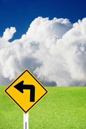 Turn left sign with nice green meadow and cloudy sky Stock Photo - 15384363