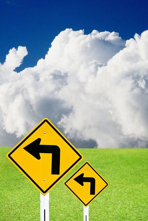 Turn left sign with nice green meadow and cloudy sky Stock Photo - 15384362