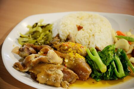 Pork leg with rice with vegetable in white dish photo