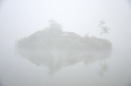 House on island in the lake with foggy background photo