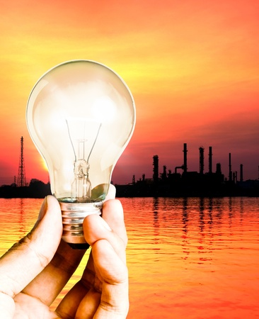 Hand hold the light bulb with oil refinery, Save power concept photo
