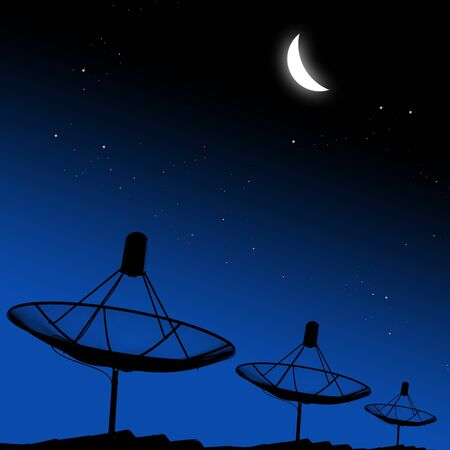 Satellite dishes on rooftop with moon in night sky photo