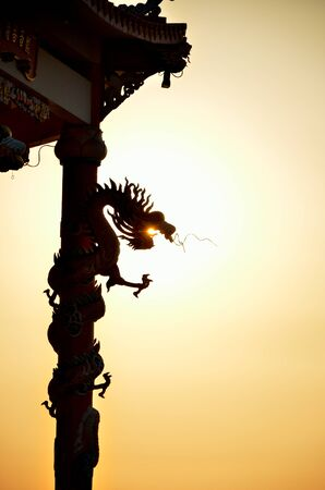 Dragon roll column statue silhouette with sunset background, Dragon eating the sun concept photo