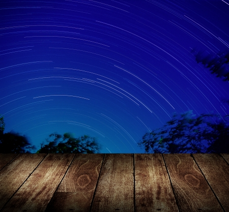 Wooden terrace with star trails background photo