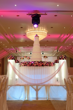 Wedding cake with rose flower decorate in ballroom  photo