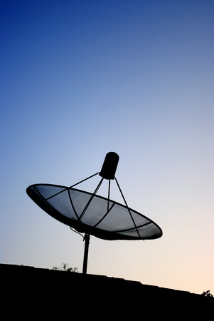 Satellite dish silhouette with blue sky background  photo