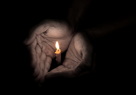 christian candle: Candle light in hand, Prayer concept Stock Photo