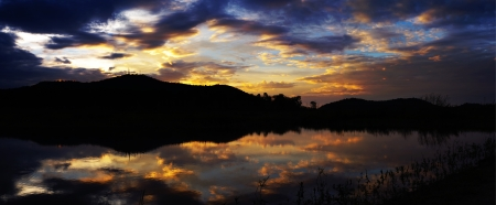 Panorama view of sunset sky with mountain silhouette and water in reservoir, Bang-pra, Chonburi, Thailand photo