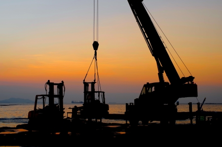 Silhouette crane working at port with sunset sky background