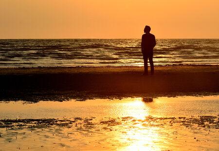Hombre de la silueta en la playa con el fondo del cielo puesta de sol, Tailandia Foto de archivo