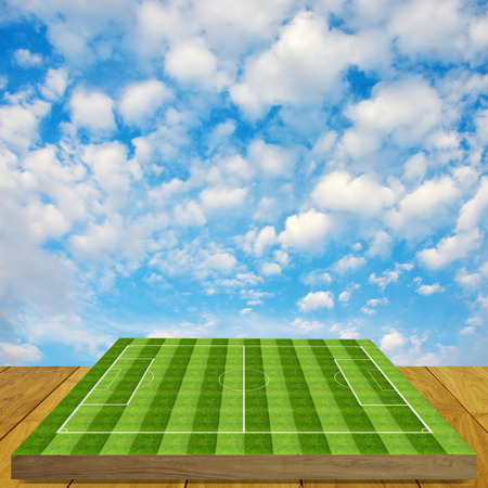 Soccer field board game on wooden floor with nice sky background photo