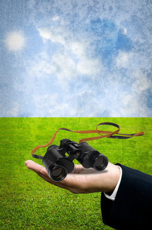 Binocular in hand with field background photo