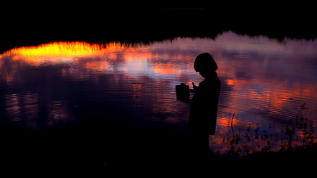 Silhouette of child beside the swamp with sunset sky reflected photo