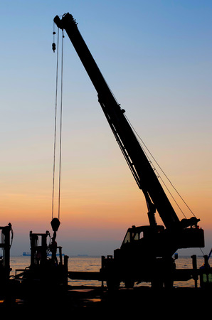 Silhouette crane working at port with sunset sky background photo