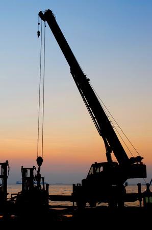cielo atardecer: Silueta de la gr�a de trabajo en el puerto con el fondo del cielo del atardecer