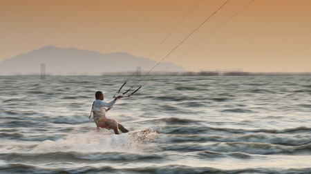 panning shot: CHONBURI, THAILAND - FEBRUARY 7,Sportman play kite surf on Fabruary 7, 2014 in Bangsean, Chonburi, Thailand