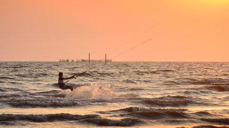 panning shot: CHONBURI, THAILAND - FEBRUARY 7 : Sportman play kite surf on Fabruary 7, 2014 in Bangsean, Chonburi, Thailand