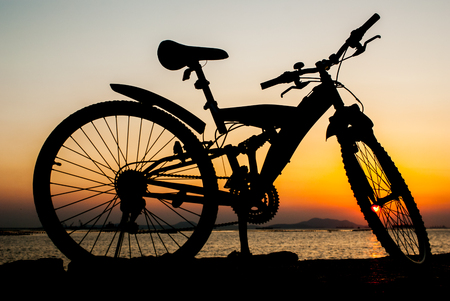 bike parking: Silhouette of mountain bike parking on jetty beside sea with sunset sky background Stock Photo