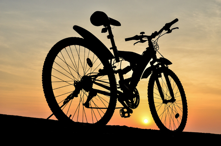 Silhouette of mountain bike parking on jetty beside sea with sunset sky background photo
