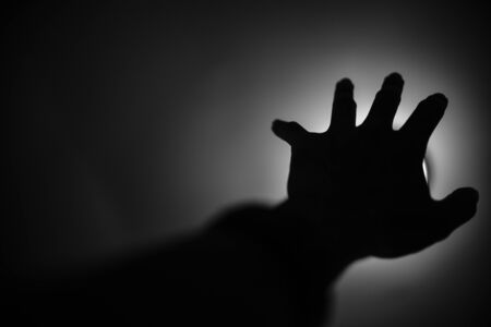 hopelessness: Silhouette of hand reaching to light Help me concept Stock Photo