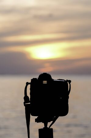 beside: Silhouette of Digital camera beside sea at sunset time Stock Photo