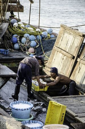 chonburi: CHONBURI, THAILAND - MAR 4 :  Unidentified worker carry fish basket to jetty on 4 March, 2015 in Chonburi, Thailand Editorial