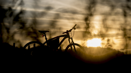 off road biking: Silhouette of mountain bike with sunset light, Trave by bicycle concept