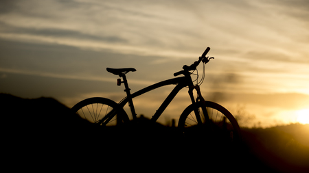 off road biking: Silhouette of mountain bike with sunset light, Cycling for travel concept
