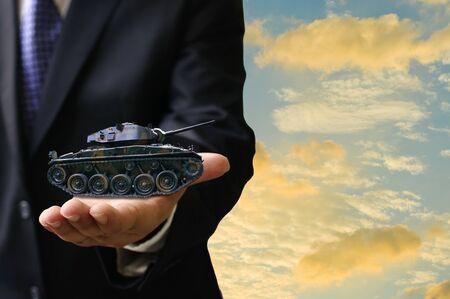 tanque de guerra: War business concept, Businessman offer war tank in hand Foto de archivo