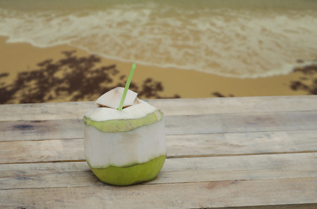 coconut drink: Coconut drink on wooden table with beach background