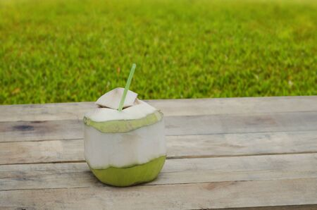 coconut drink: Coconut drink on wooden table with green grass background Stock Photo