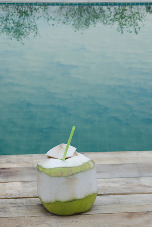 coconut drink: Coconut drink on wooden table at swimming pool